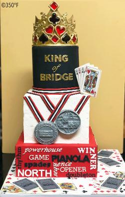 A tiered cake for an international bridge player's milestone birthday with sugar recreations of medals he won in his career.