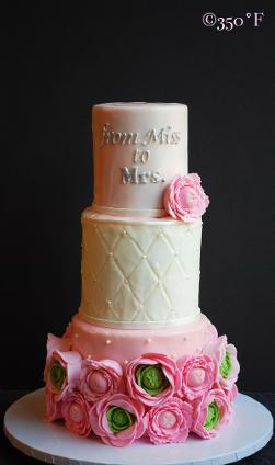 A bridal shower tiered cake adorned by sugar ranunculuses