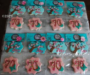 Floral cookies packaged beautifully in pink and turquoise as party favors for guests of a 70th birthday party