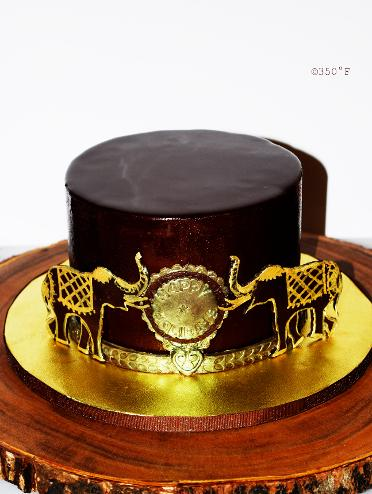 A holiday cake for an indonesian family - a chocolate mirror glaze cake with gold accents
