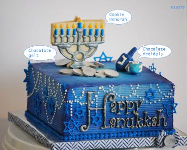Hanukkah cake with cookie and chocolate dreidels, menorah and gelt.