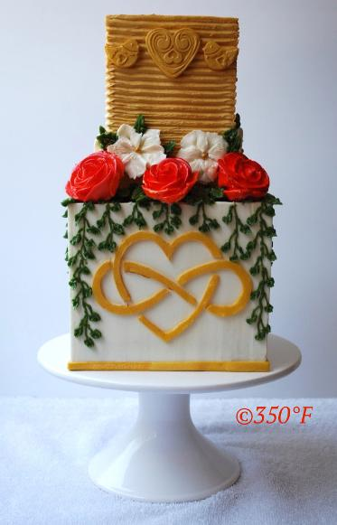 A two tier buttercream wedding cake with lovebirds, roses and infinite love monogram