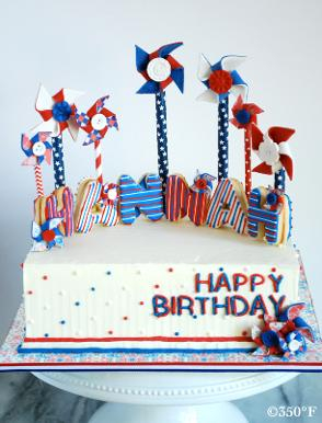 A july 4th themed birthday cake with pinwheels made out of chocolate and name spelt with cookies