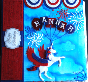 A birthday cake that combines July 4th and Unicorn themes with fireworks and red, blue, white decorations