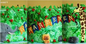 A jungle themed first birthday cake with jungle friends decorating the forest for the celebrations