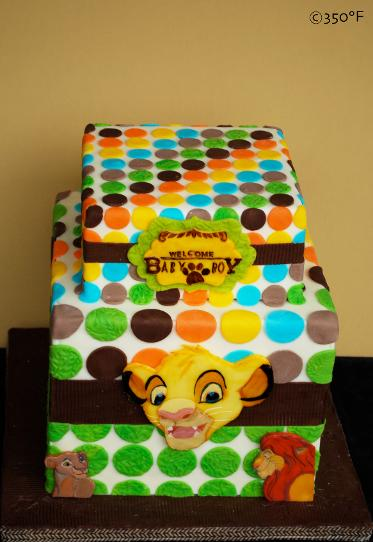 A Lion King themed tiered baby shower cake with multicolored polka dots