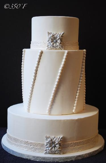 A jeweled wedding cake with ornate brooch and pearl strings