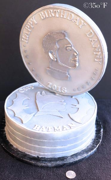 A batman themed cake created as a stack of Gotham City currency coins with a profile of Batman on one side and the profile of Danny on the other.