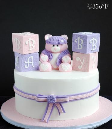 A baby shower cake with edible baby blocks and a teddy bear welcoming a baby girl.