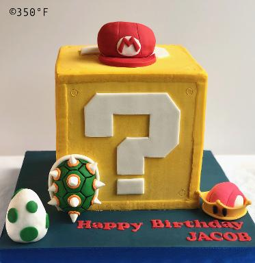 super mario birthday cake with mario cap, pricess crown, the egg and the shell of Bowser