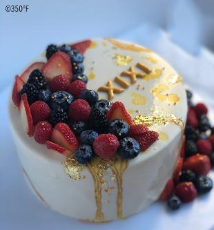 mirror glaze cake with fresh berries and 24K gold leaf decorations