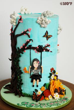 A personalized spring themed tall birthday cake with flowers, cherry blossom tree, butterflies and an appliqué of the birthday girl on a swing