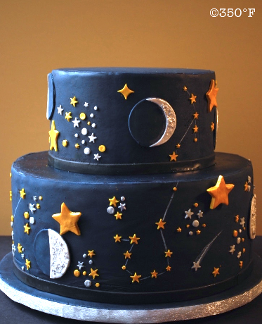 A celestial two tiered sweet 16 cake in navy, with constellations, phases of the moon and a shooting star on which to wish for!