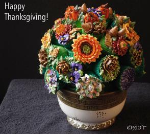A Thanksgiving cupcake bouquet with pumpkin pie spice cupcakes decorated with colorful fall flowers and foliage