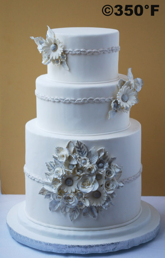 a white and silver wedding cake with a bunch of flowers