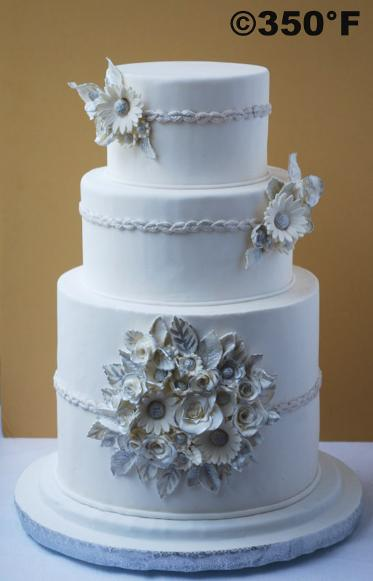 A white and silver wedding cake with a bunch of silver gilded flowers