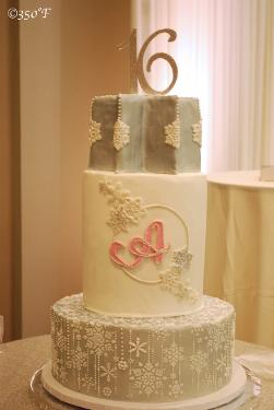 A three tiered snowflake themed sweet 16 cake with monogram and a sculpted top tier