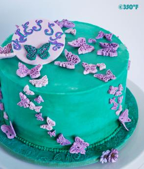 Turquoise and purple birthday cake with a flock of butterflies