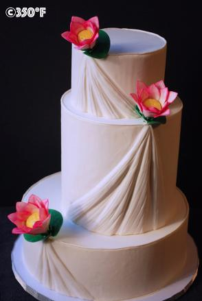 A white wedding cake with pleats and lotus. A cake that gives the impression of a wedding gown.
