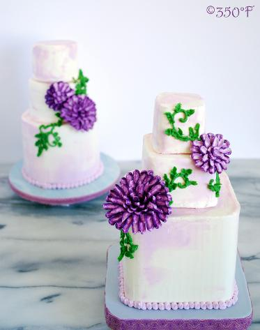 Floral mini tiered cakes as center pieces for guest tables at a wedding reception