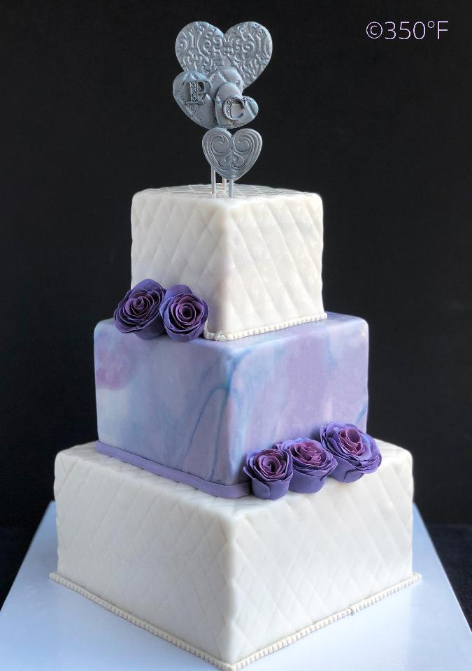 Classic diamond weave tiers separated by a ethereal lavender marbled tier topped with custom made edible silver monogram for a wedding